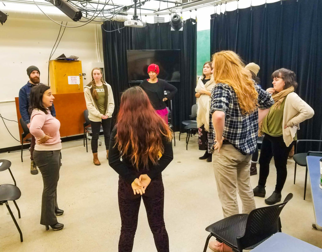 Students in a theatre classroom standing in a circle listening to Erica, at left, hands on her hips.